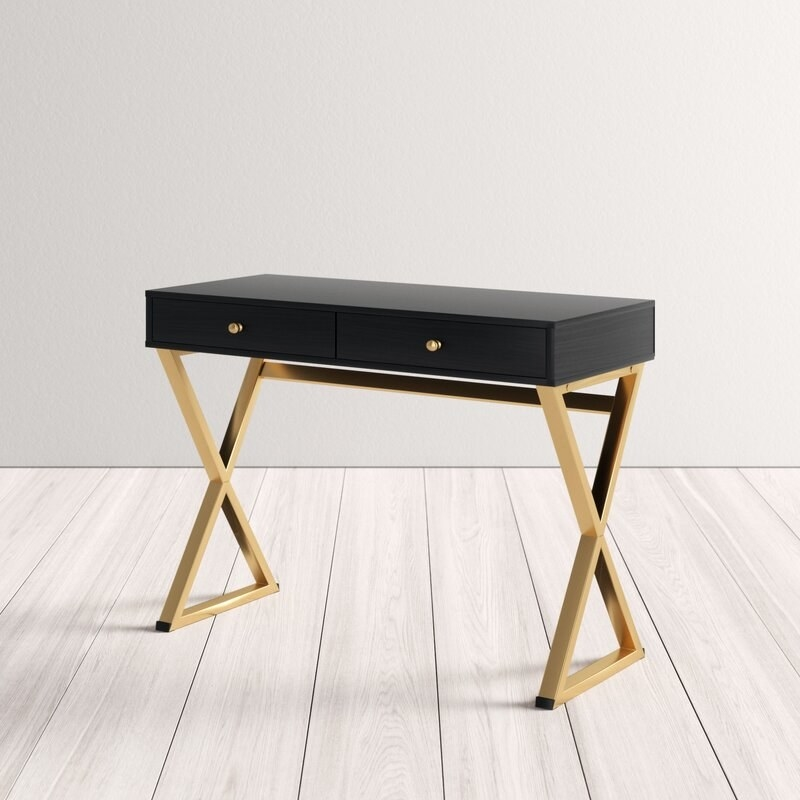 Black-top desk with two drawers with gold knobs and gold crossing legs