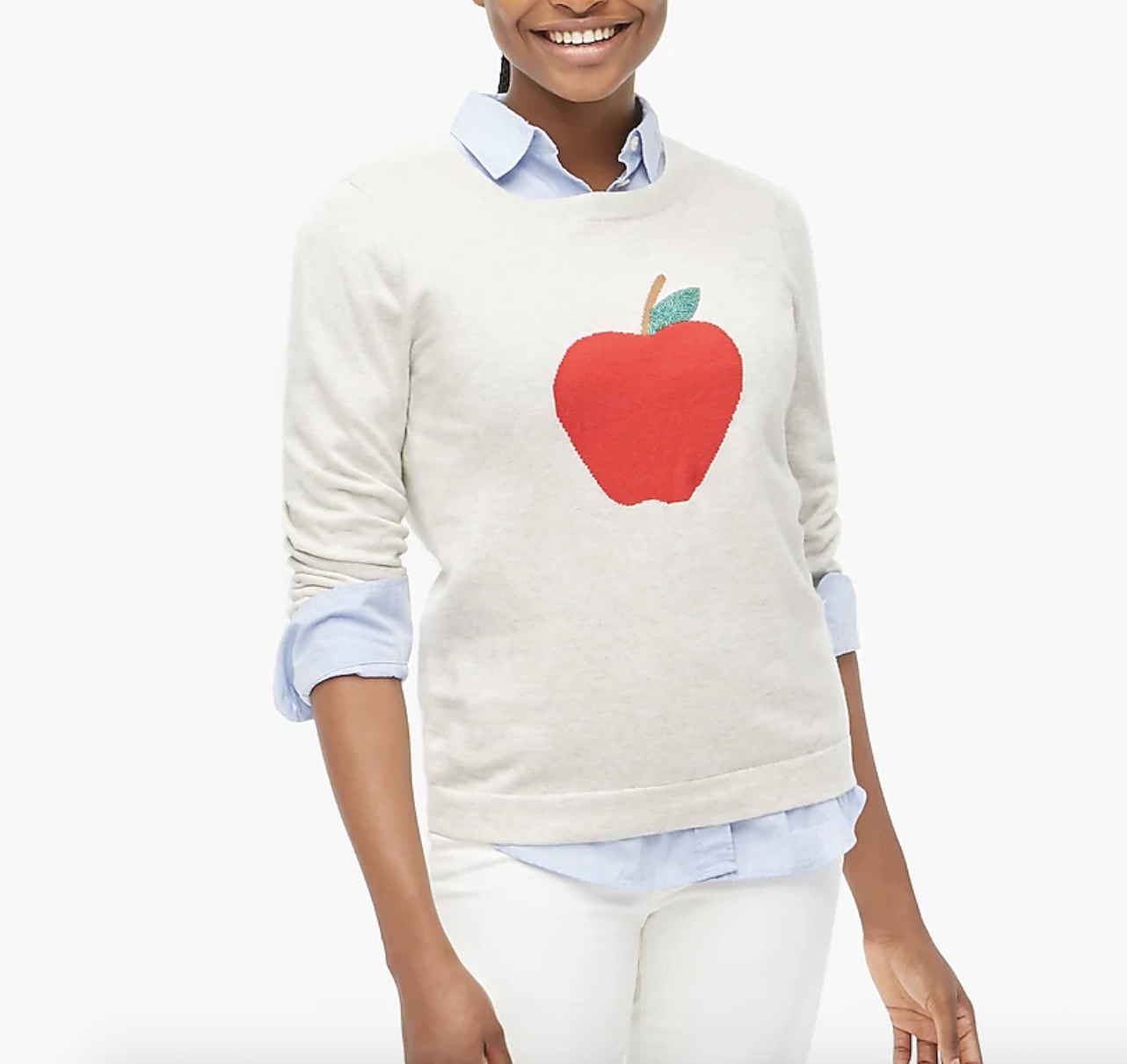 a model in a white crew neck sweater with a red apple icon on it