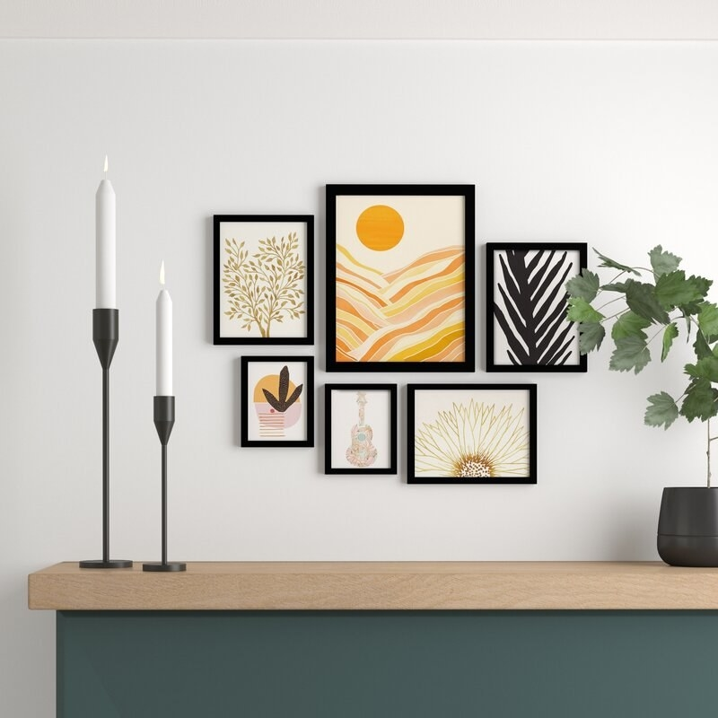 Six art prints of different sizes with graphic illustrations of nature and plants, and a guitar in black frames on a wall