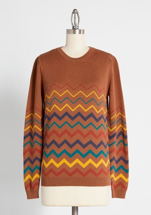 the brownish orange sweater with stripes in blue, turquoise, orange, and yellow