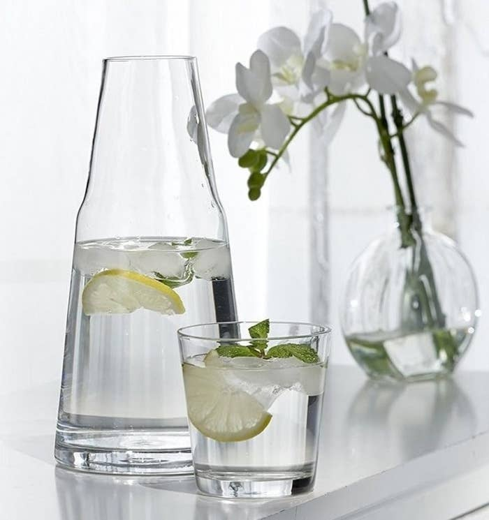 A glass pitcher and matching glass cup