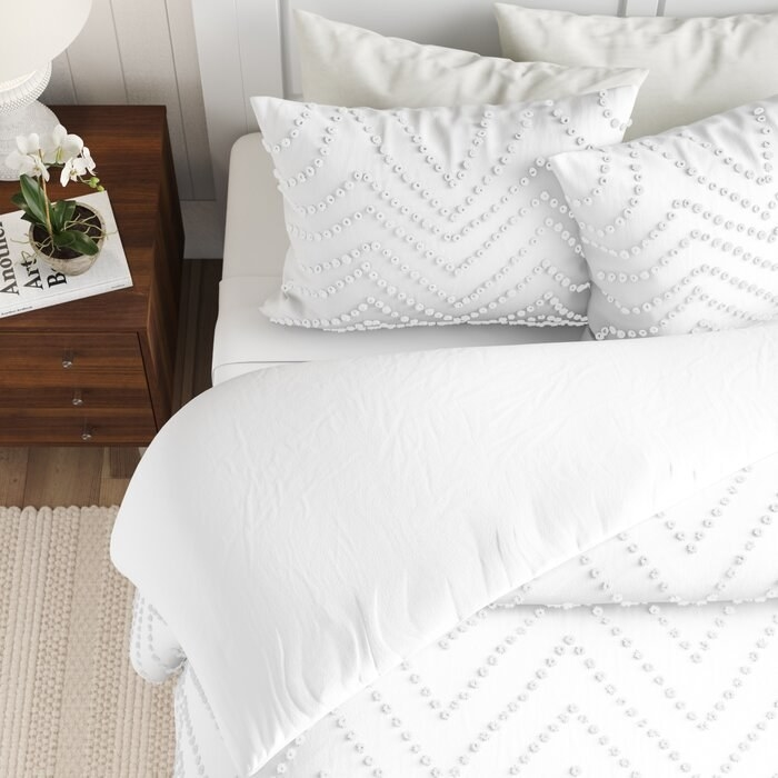 Closeup of the White Freya Reversible Comforter Set on a bed