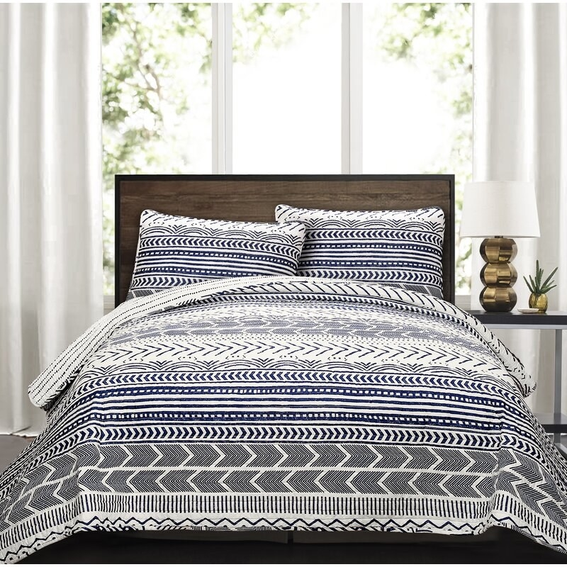 The quilt with the chevron, line, and dotted pattern in blue and black up and two pillows with the matching pattern on it.