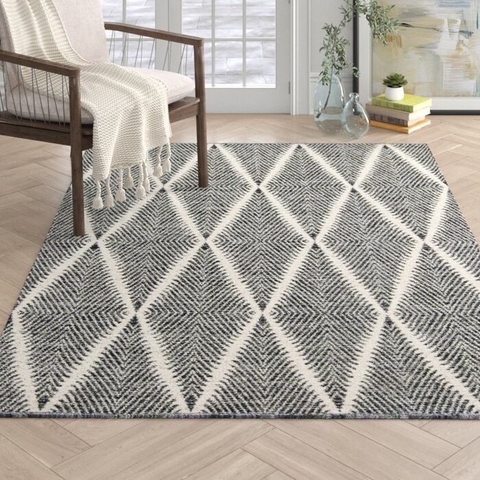 The black and white River Geometric Handmade Flatweave in a decorated sitting area