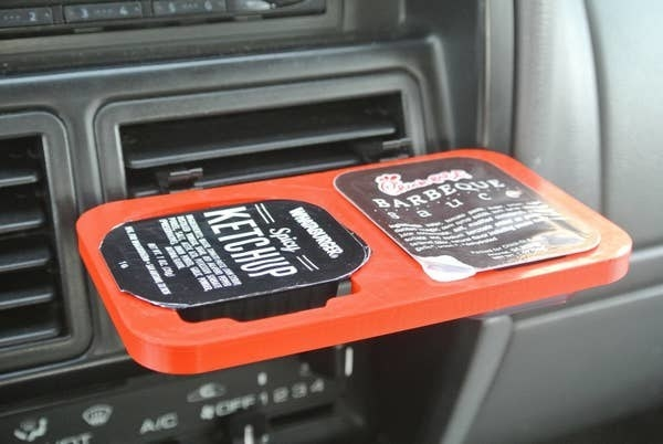 The orange double dipper clip clipped to a car air vent holding ketchup and barbecue sauce