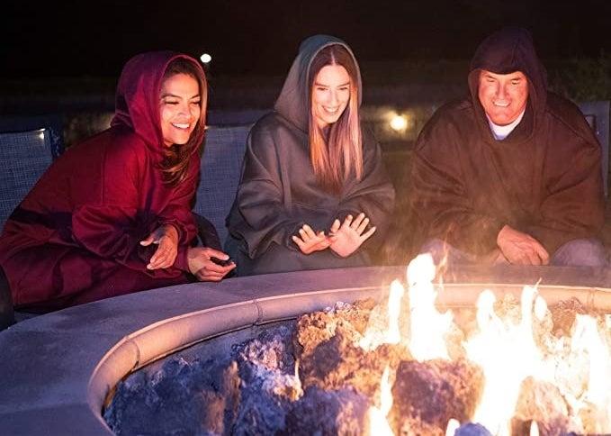 People wear oversized sweaters around a firepit