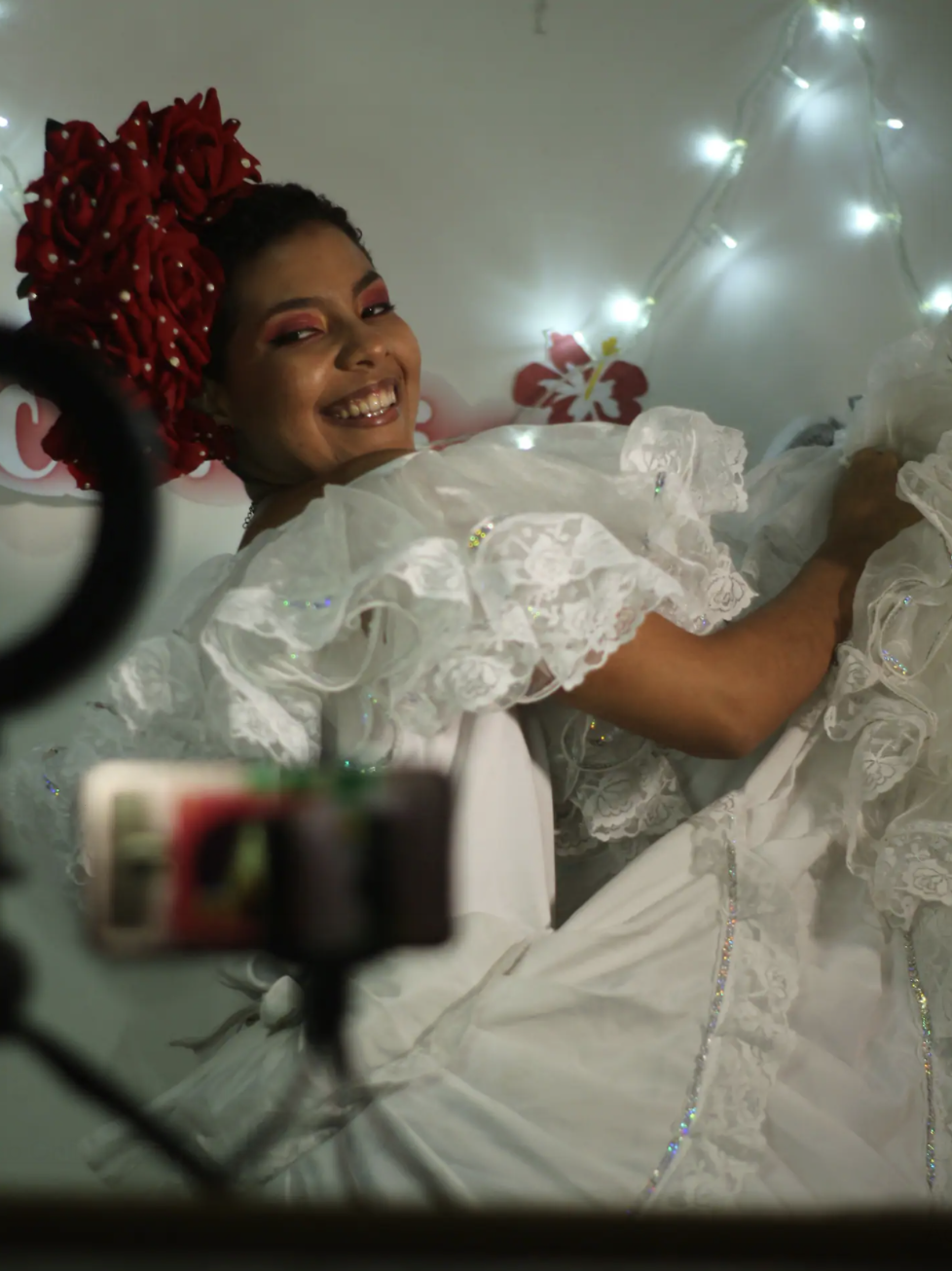 A woman in traditional white, swishy dress and rose hair piece smiles and lifts up her skirts in a dance motion to a camera