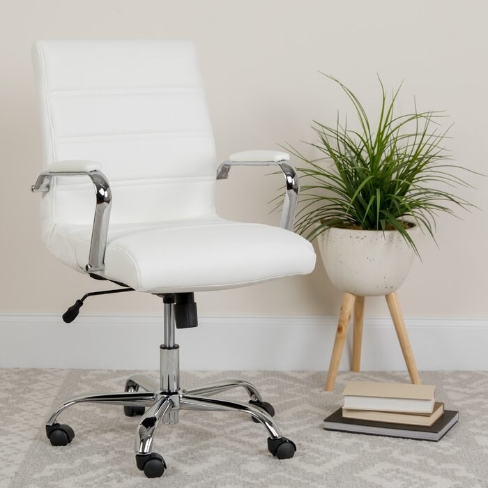 The white Leaman Ergonomic Executive Chair propped next to a standing planter