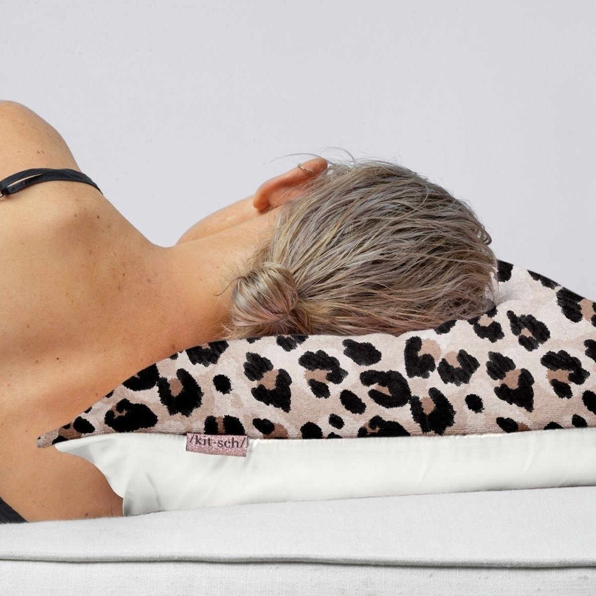 A model sleeping on a leopard print pillowcase with white lining underneath