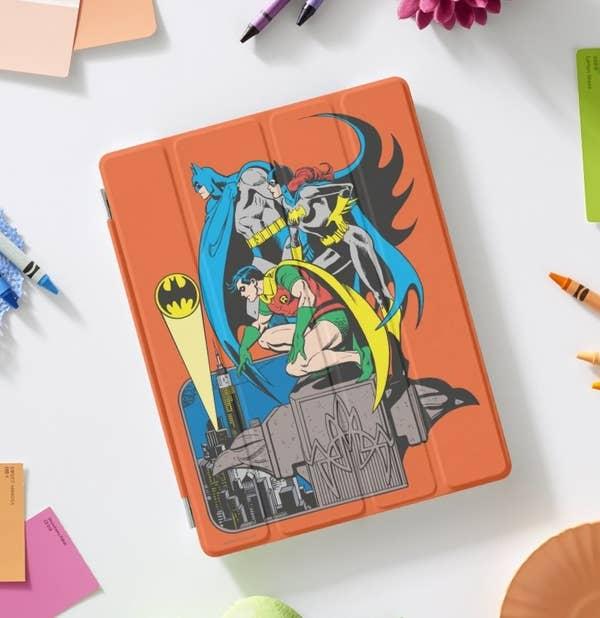 An orange iPad cover featuring artwrok of Batman, Batgirl, and Robin
