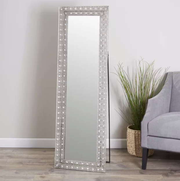 Studded silver rectangle mirror propped against wall next to gray couch