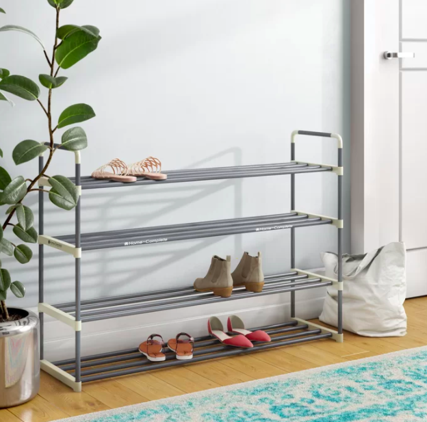 Silver and white four-tier storage rack with olive boots, red flats, and light pink sandals against a hallway wall