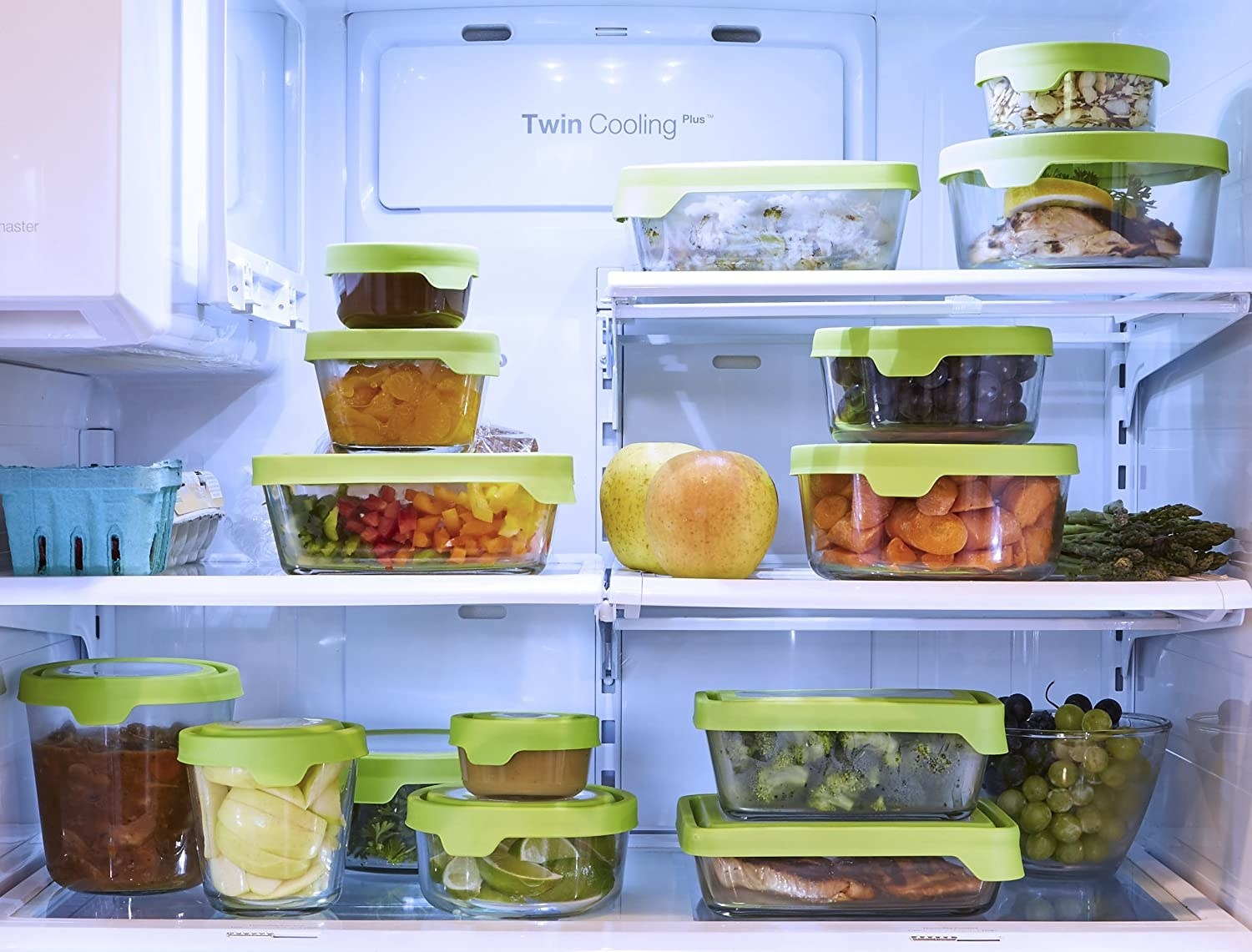 A variety of sizes of the the containers filled with different types of food in a refridgerator