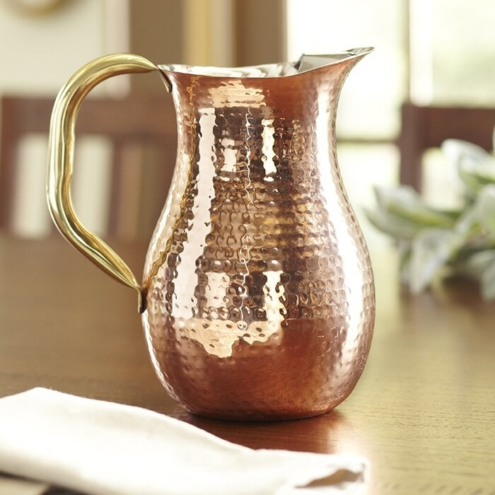 The Copper Serving Hammered Pitcher on a wooden table