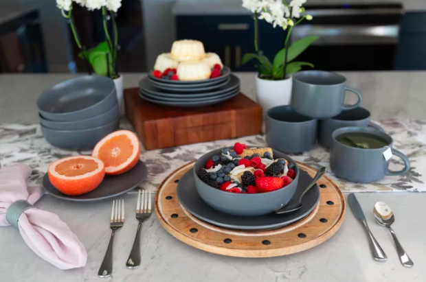 Dark gray dinnerware set complete with bowls, mugs, and small plates on a kitchen table before breakfast