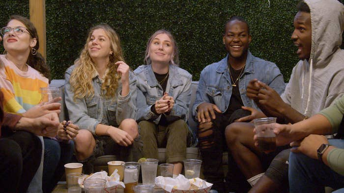 (L-R): Students at Gallaudet University, Renate Rose, Alexa Paulay-Simmons, Cheyenna Clearbrooke, Daequan Taylor and Rodney Burford, sit around a table with food and beverages on it