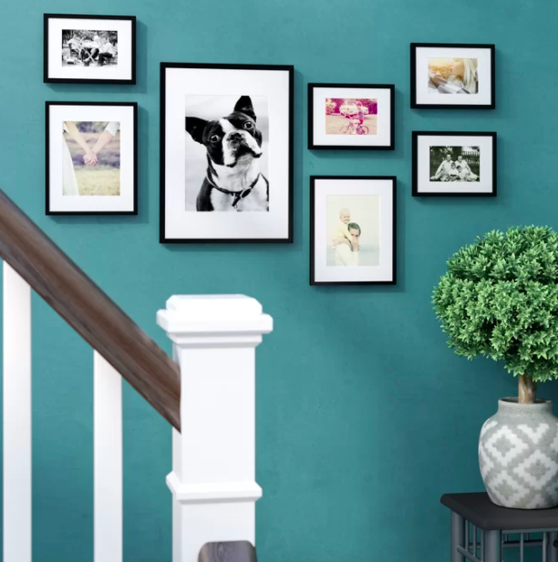 Seven black photo frames arranged in a gallery on the wall next to a staircase