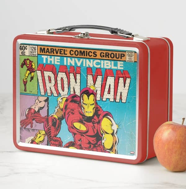 A metal lunchbox with a black plastic handle featuring a classic Iron Man comic cover
