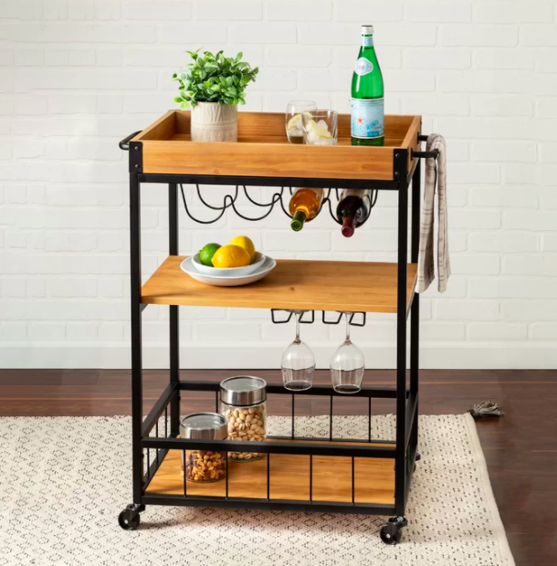 Wood and black rolling bar cart with three shelves and nooks for wine bottles, glasses, and more barware