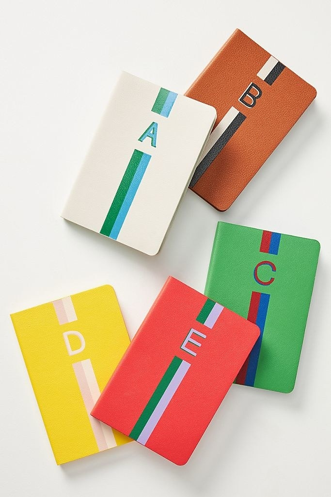 Brightly colored journals with a vibrant striped design, each personalized with a letter on the cover