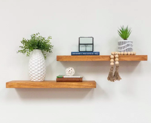 Walnut-tone floating shelves storing plant vases, books, and other decorations on a bare white wall