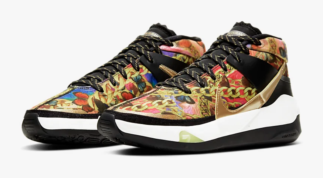 The sneaker features a multicolor print of butterflies and chains with gold and black details on the swish, sole, and laces
