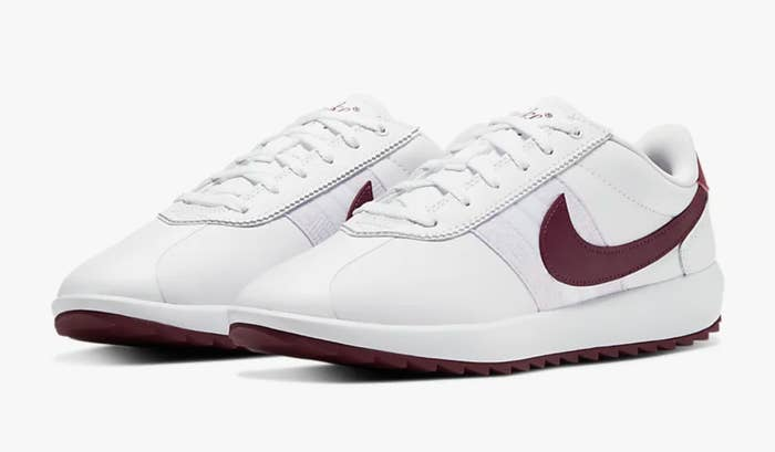 The sneakers in white with maroon swishes and bottoms