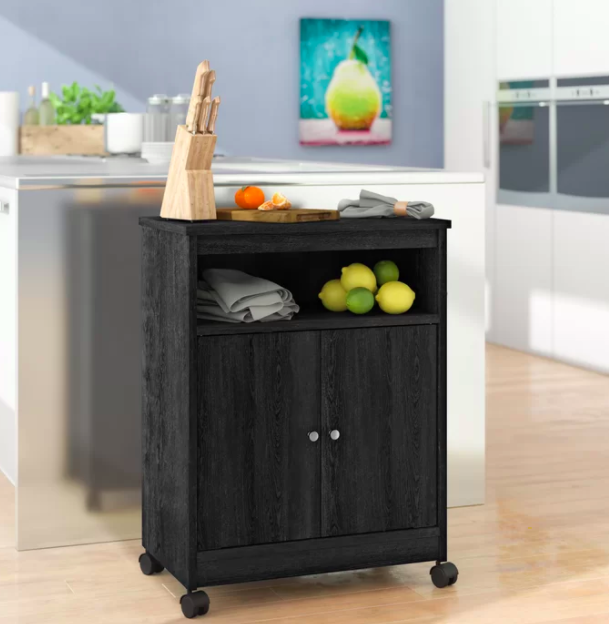 Black wheeling pantry with an upper shelf filled with lemons and limes and a storage cabinet at the bottom