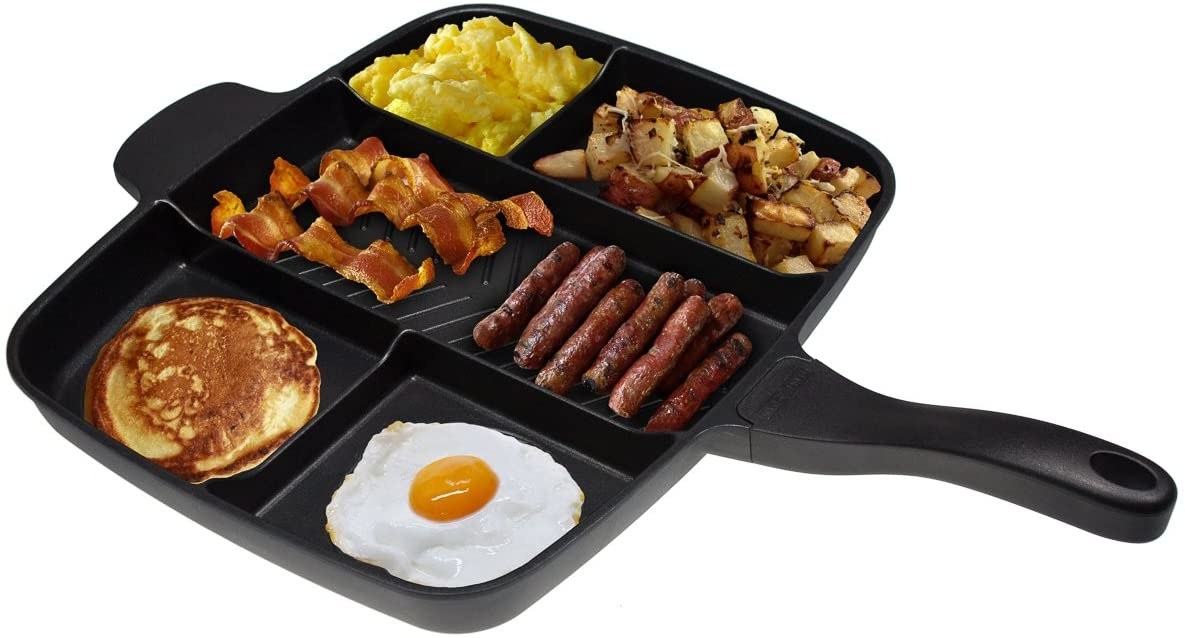The skillet showing how many things it can cook at once, fitting scrambled eggs, potatoes, bacon, sausage, a pancake, and a fried egg into all of its compartments