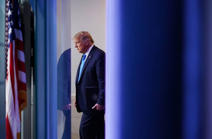 President Donald Trump stands behind a blue curtain and US flag