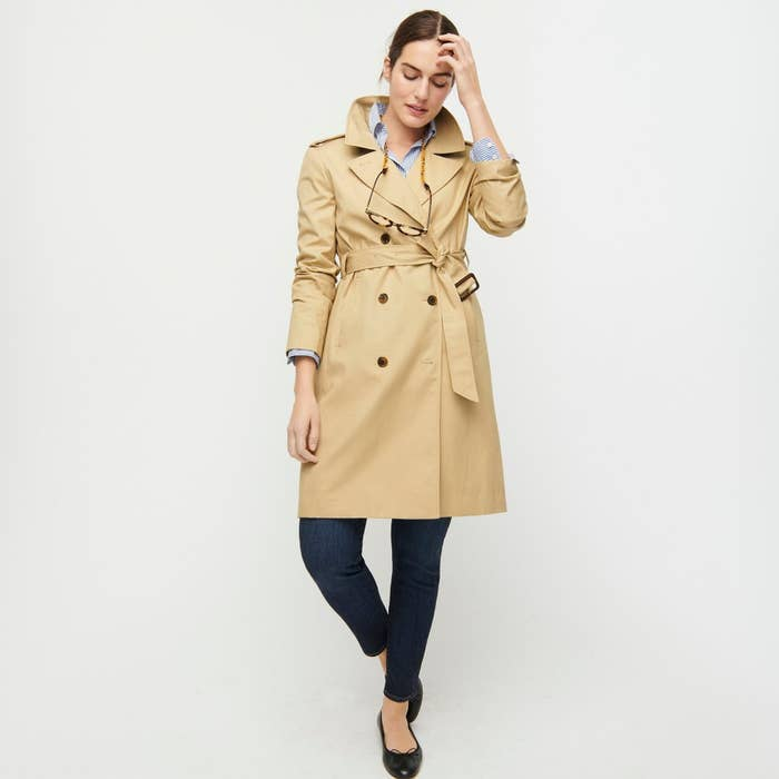 Model wearing double-breasted belted trench coat in classic beige
