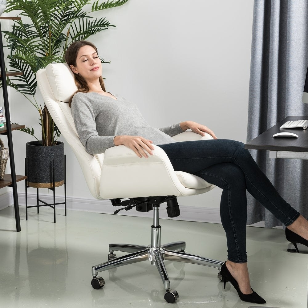 Model reclining on the white faux-leather chair