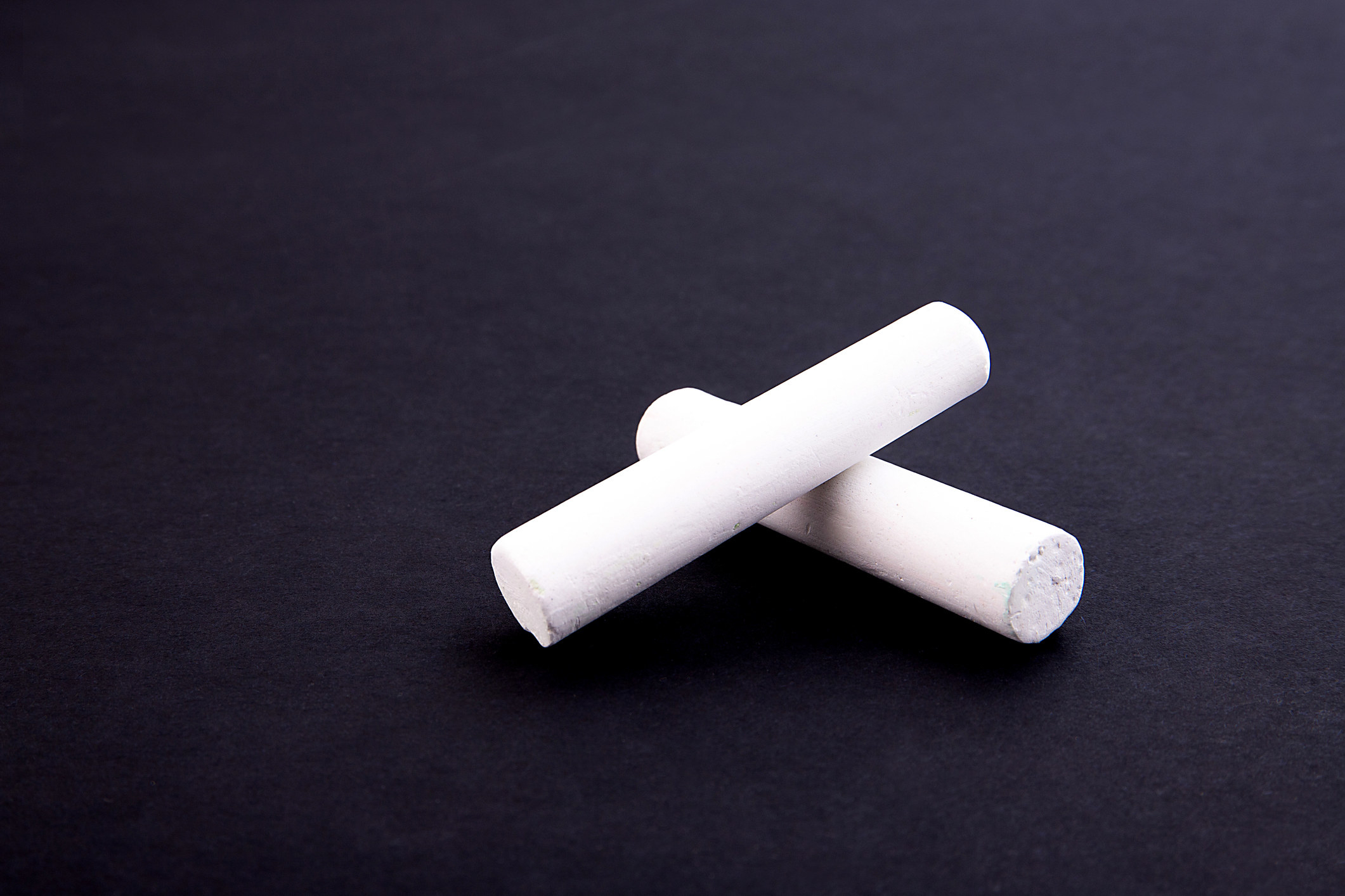 Two white crayons on a black background
