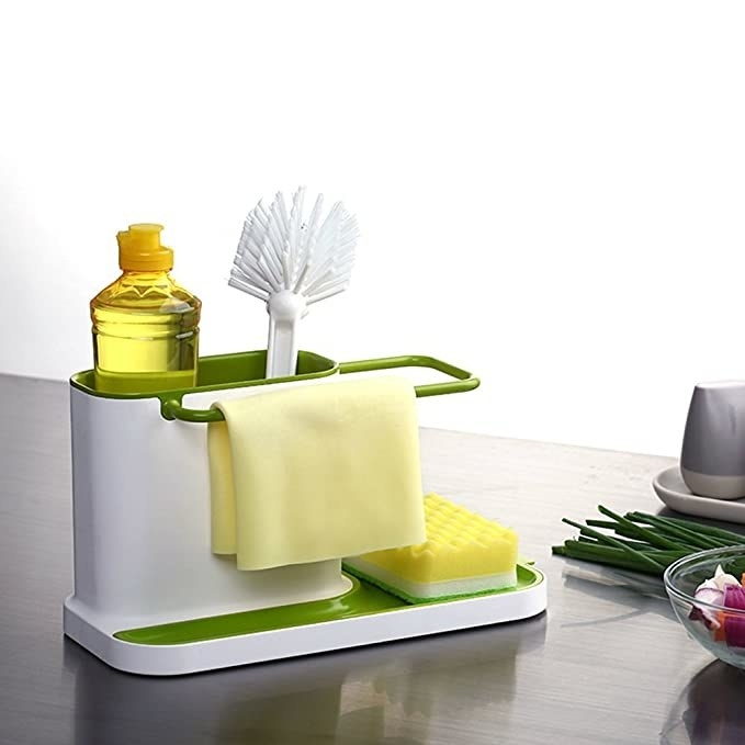 The sink caddy with a sponge, brush, cleaning detergent and a cleaning cloth in it.