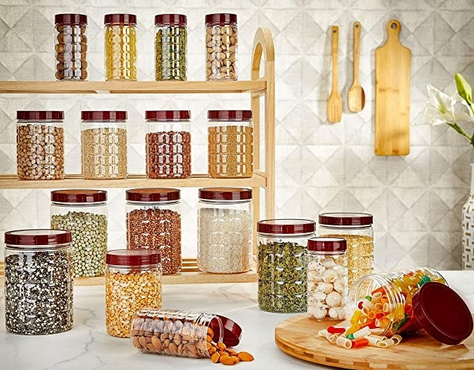Containers on a shelf with nuts, grains, pulses, cereals and pasta in them.