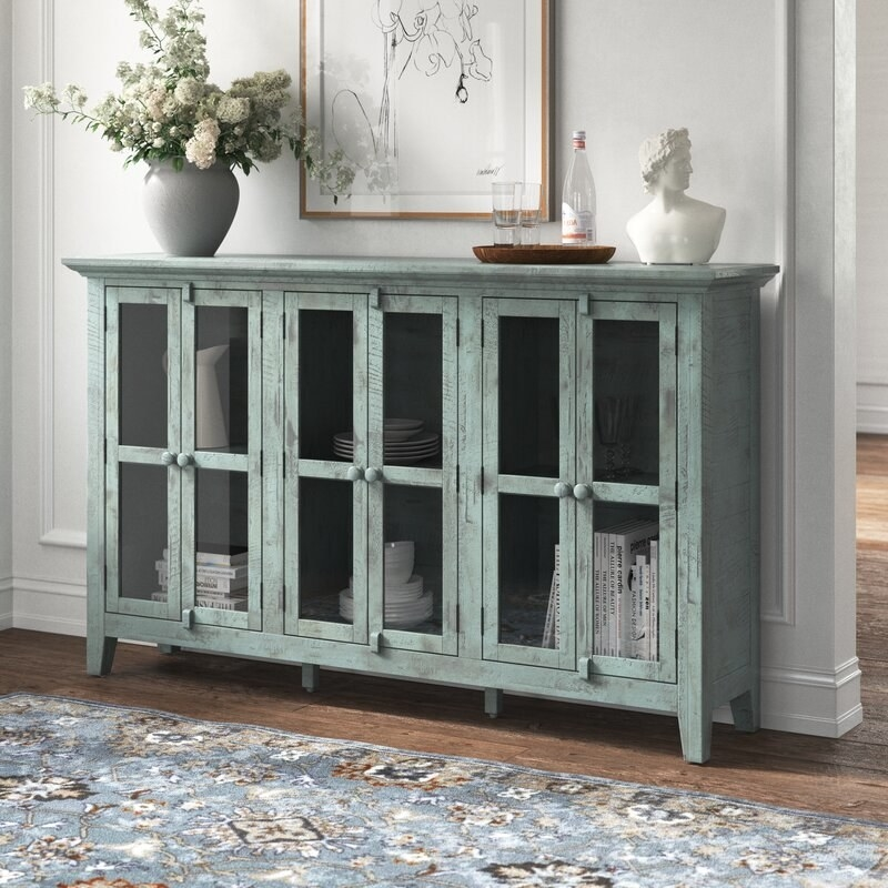 The blue-green sideboard, which has four rectangular panes of glass in the three doors