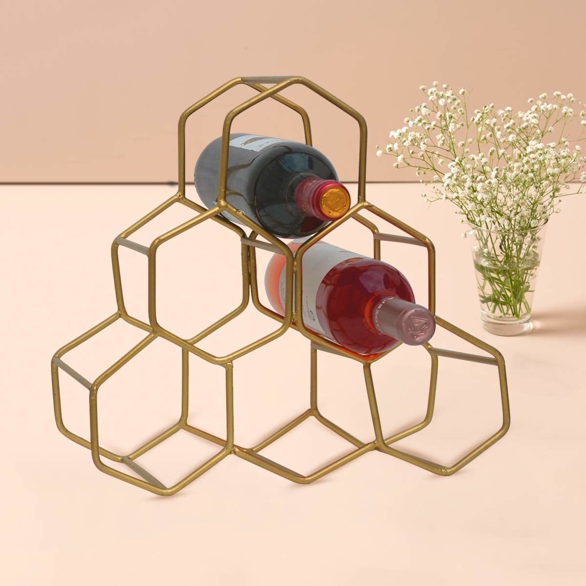 A honeycomb pyramid style golden wine rack with 6 slots pictured with wine bottles.