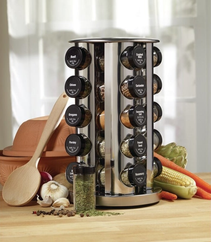 Stainless steel spice rack with jars and black lids with the labels on top