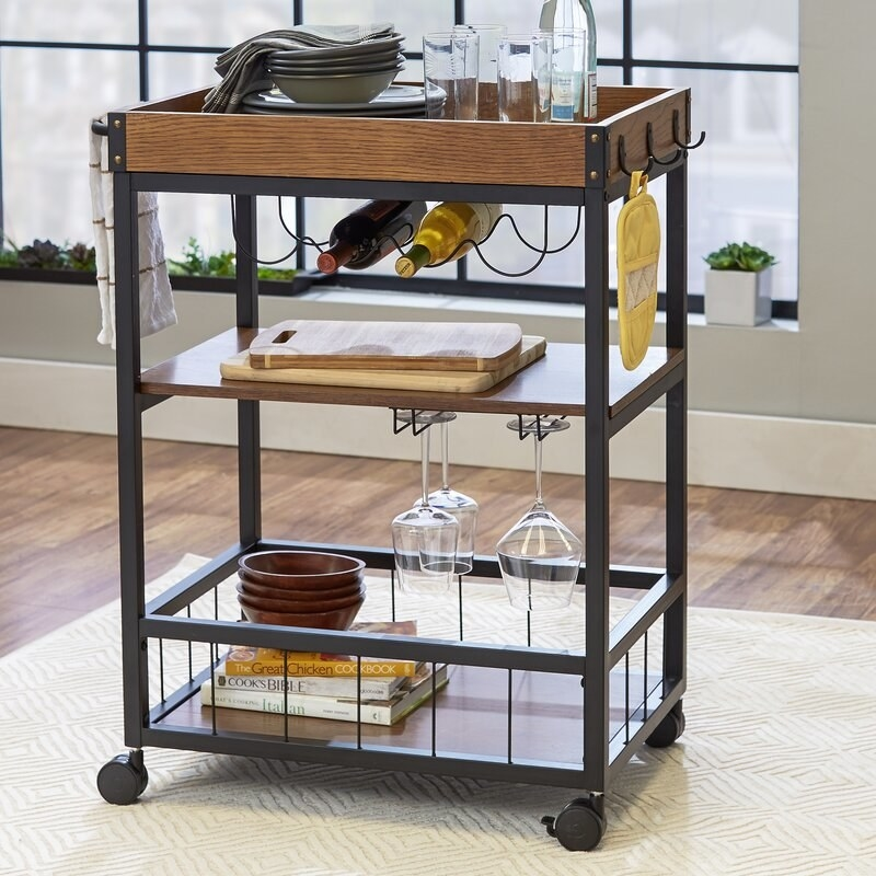 Styled bar cart holding wine glasses, wine bottles, and other bar essentials