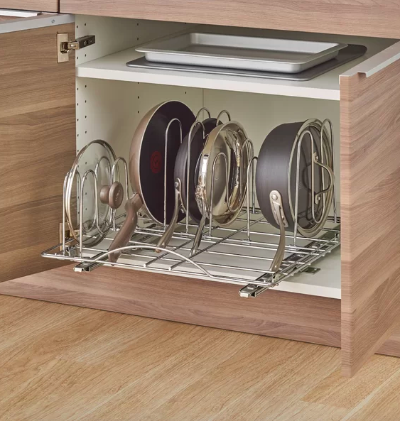 Flat organizer sliding out of cabinet with wire stands holding five different pots, pans, and lids