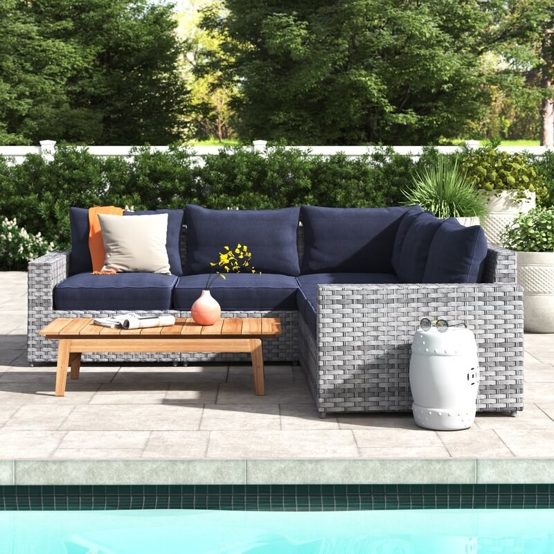 The gray wicker L-shaped sectional with navy cushions