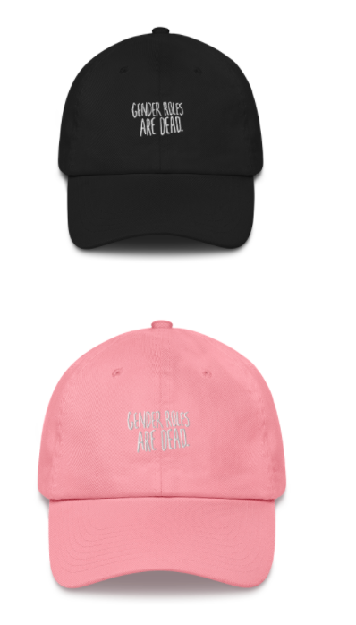 "two hats, one black and one pink that read ""gender roles are dead"""