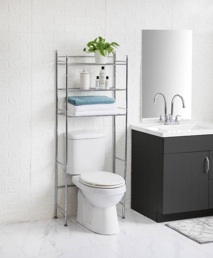 The bathroom storage unit being used to hold towels and toiletries.