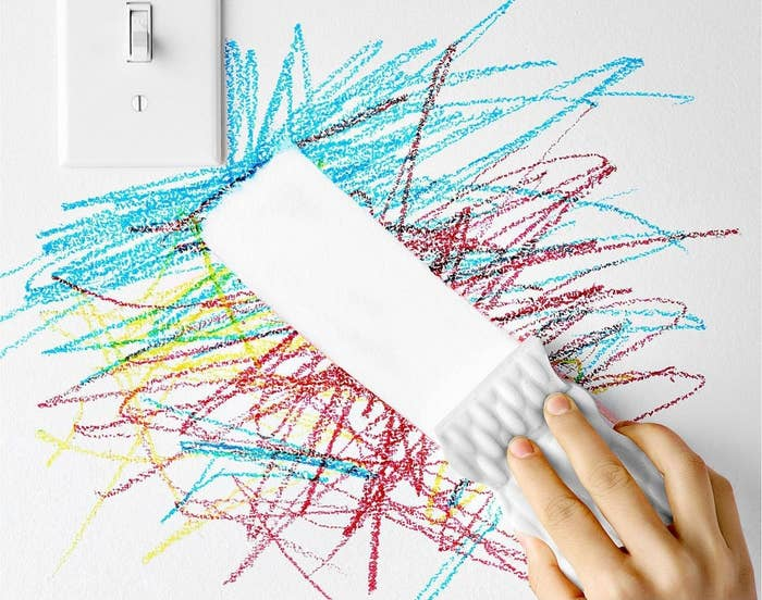 person using magic eraser to get rid of crayon marks on the wall