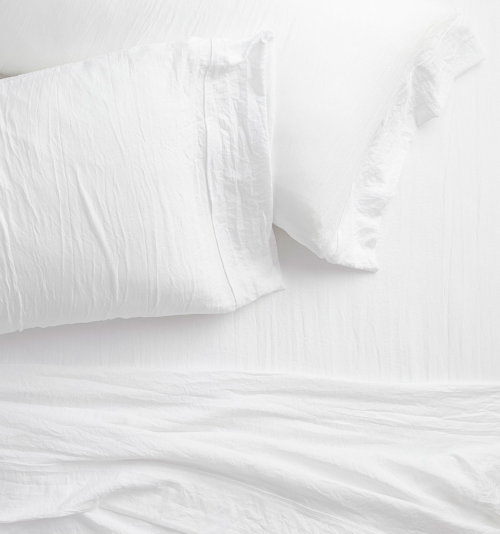 Two pillows on a bed with a top sheet