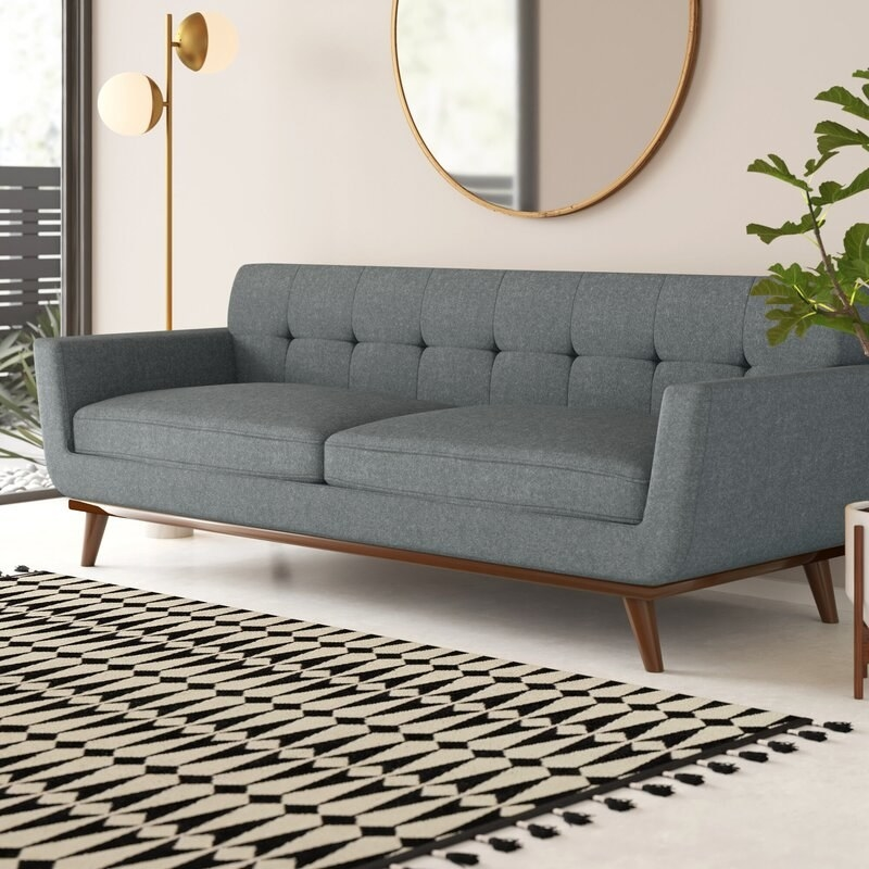Grey couch with two cushions and a tufted back with brown wood legs