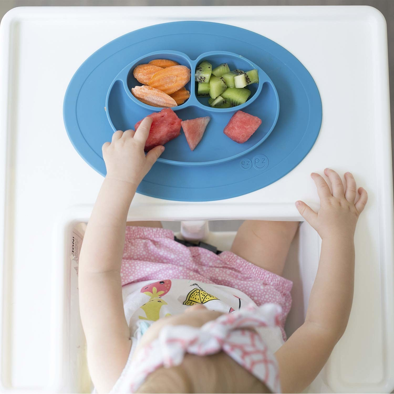 A baby sitting in a high chair with the blue, oval-shaped mat stuck to it. It's got three compartments that form a happy-face like shape in the center