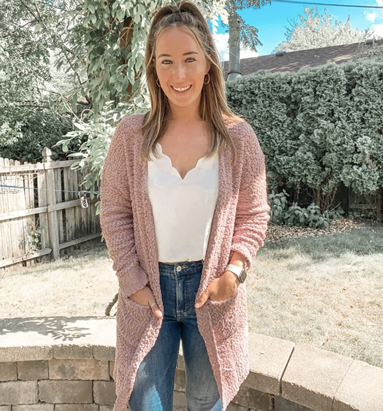 reviewer wearing pink sleeved midi-length cardigan with pockets