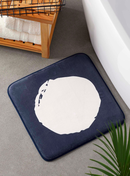 The bath mat neatly placed next to a large bathtub
