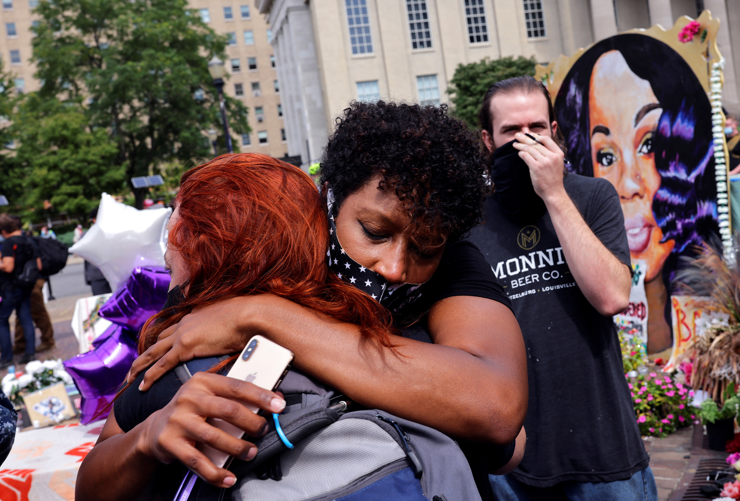 Two women embrace in front of a memorial to Breonna Taylor